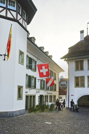 crown spire: THUN, SWITZERLAND - JANUARY 1, 2014: Krone Hotel and Flags in the City Hall Square of Thun. Thun is a city in Swiss canton of Bern, where Aare river flows out of Lake Thun Editorial