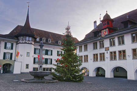 crown spire: Town Hall Square with a Christmas tree in the Old Town of Thun. Thun is a city in Swiss canton of Bern, where Aare river flows out of Lake Thun. Town Hall Square is a historic center of the city