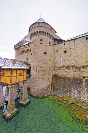 leman: VEYTAUX, SWITZERLAND - JANUARY 2, 2015: Entrance tower and wall to Chillon Castle. It is an island castle on Lake Geneva (Lac Leman) in the Vaud,between Montreux and Villeneuve. Editorial