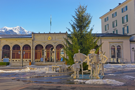 st gallen: BAD RAGAZ, SWITZERLAND - JANUARY 5, 2015: Spa house with People monument and Mountains. Bad Ragaz is a city in St. Gallen in Switzerland, over Graubunden Alps. Spa and recreation is at Tamina valley Editorial