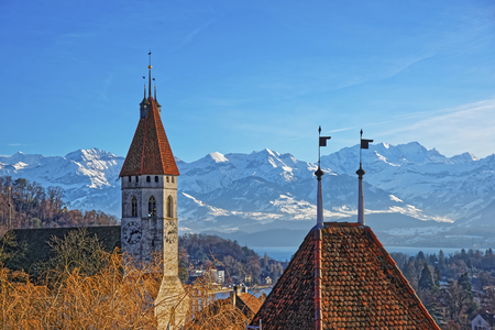 monch: Panorama of Thun City Church with Thunersee and Alps in winter. Thun is a city in the canton of Bern in Switzerland, where the Aare river flows out of Lake Thun. There is a view of Bernese Alps.