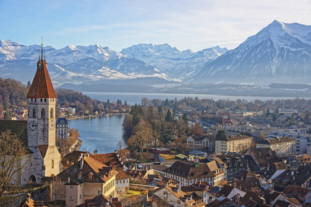 monch: Panorama of City Church and Town of Thun with Alps and Thunersee. Thun is a city in the canton of Bern in Switzerland, where the Aare river flows out of Lake Thun. There is a view of Bernese Alps. Stock Photo