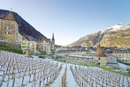 january sunrise: CHUR, SWITZERLAND - JANUARY 5, 2015: St Martin Church and vineyard of Chur at sunrise. Chur is the capital of canton Graubunden in Switzerland. It lies in the Alpine Grisonian Rhine valley. Editorial