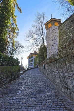 town hall square: Small Cobblestone paved road in the Old City of Thun. Thun is a city in Swiss canton of Bern, where Aare river flows out of Lake Thun. Town Hall Square is a historic center of the city Stock Photo