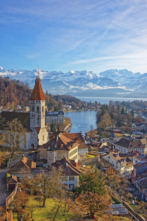 monch: Panorama of Thun Town and Church with Alps and Thunersee. Thun is a city in the canton of Bern in Switzerland, where the Aare river flows out of Lake Thun. There is a view of Bernese Alps.