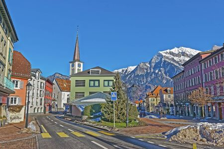 st gallen: Catholic Church and Mountains in Town of Bad Ragaz. Bad Ragaz is a city in canton St. Gallen in Switzerland.  It lies over Graubunden Alps. Spa and recreation village is at end of Tamina valley Stock Photo