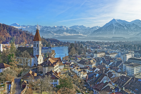 Panorama of Thun Church and City with Thunersee and Alps. Thun is a city in the canton of Bern in Switzerland, where the Aare river flows out of Lake Thun. There is a view of Bernese Alps.