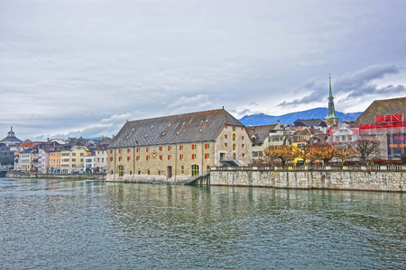 jura: Waterfront and Clock Tower with Landhaus in Solothurn. Solothurn is the capital of Solothurn canton in Switzerland. It is located on the banks of Aare and on the foot of Weissenstein Jura mountains Stock Photo