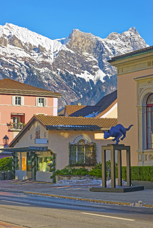 st gallen: BAD RAGAZ, SWITZERLAND - JANUARY 5, 2015: Cat statue and Mountains. Bad Ragaz is a city in St. Gallen in Switzerland.  It lies over Graubunden Alps. Spa and recreation is at the end of Tamina valley