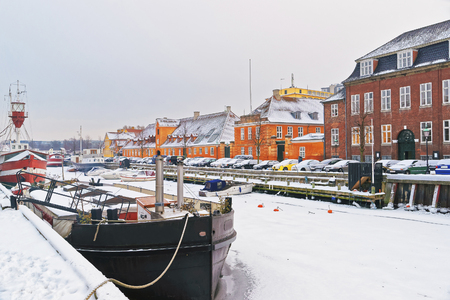 entertainment district: Nyhavn (New Harbor) in winter. It is waterfront, canal, entertainment district in Copenhagen, Denmark. It is lined by colored houses, bars, cafes, wooden ships
