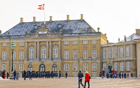 identical: COPENHAGEN, DENMARK - JANUARY 5, 2011: Guard change in Amalienborg in winter. Amalienborg is a Royal Palace in Copenhagen, Denmark. It consists of four identical classical palaces around the courtyard Editorial