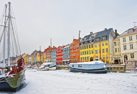 COPENHAGEN, DENMARK - JANUARY 5, 2011: Nyhavn (New Harbor)in winter. It is waterfront, canal, entertainment district in Copenhagen of Denmark. It is lined by colorful houses, bars, cafes, wooden ships