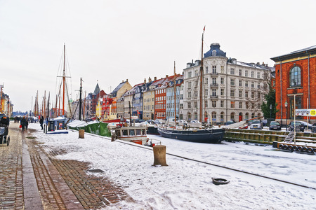 COPENHAGEN, DENMARK - JANUARY 5, 2011: Nyhavn (New Harbor) in winter. It is waterfront, canal, entertainment district of Copenhagen, Denmark. It is lined by colorful houses, bars, cafes, wooden ships