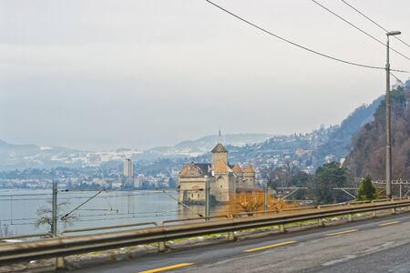 VEYTAUX, SWITZERLAND - JANUARY 2, 2015: View to Chillon Castle from the road. It is an island castle on Lake Geneva (Lac Leman) in the Vaud, between Montreux and Villeneuve. Editorial
