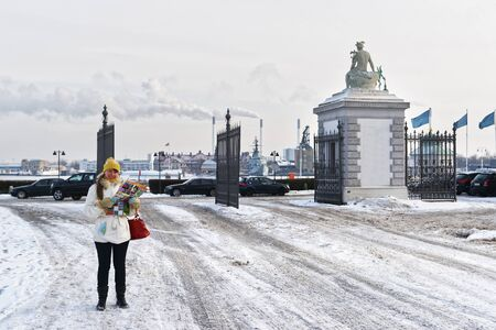 freeport: Girl holding a map at the Langelinie Gate in the park in winter Copenhagen. Langelinie is a pier, promenade and park in central Copenhagen, Denmark, and home of the statue of The Little Mermaid.