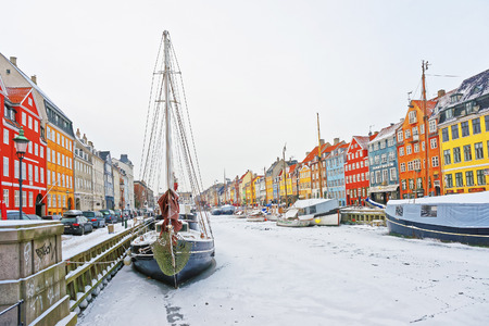 COPENHAGEN, DENMARK - JANUARY 5, 2011: Nyhavn (New Harbor)in winter. It is waterfront, canal, entertainment district in Copenhagen in Denmark. It is lined by colorful houses, bars, cafes, wooden ships