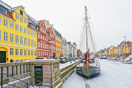 COPENHAGEN, DENMARK - JANUARY 5, 2011: Nyhavn (New Harbor)in winter. It is waterfront, canal, entertainment district in Copenhagen in Denmark. It is lined by colored houses, bars, cafes, wooden ships