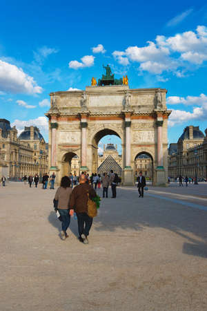 carrousel: PARIS, FRANCE - MAY 3, 2012: Triumphal Arch and Louvre Palace in Paris in France. This triumphal arch is located in the Place of Carrousel. Louvre Palace is a former royal palace and now is a museum