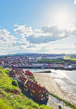whitby: Coast of North Sea in Whitby in North Yorkshire in England. Whitby is a seaside port and town on the coast of the river Esk.