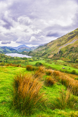snowdonia: View to a mountain lake in Snowdonia National Park in North Wales of the United Kingdom. Snowdonia is a mountain range and a region in North of Wales.