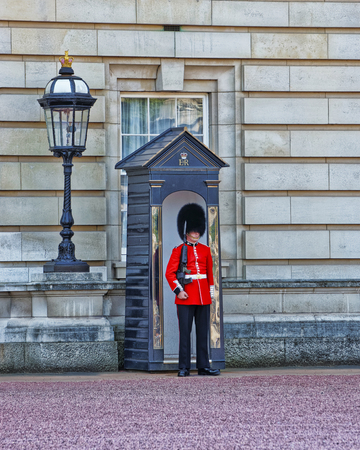 residences: LONDON, ENGLAND - APRIL 30, 2011: Queen Guard at his post at Buckingham Palace in London in England. Queen Life Guard is a cavalry and infantry soldier who guards royal residences in the UK.