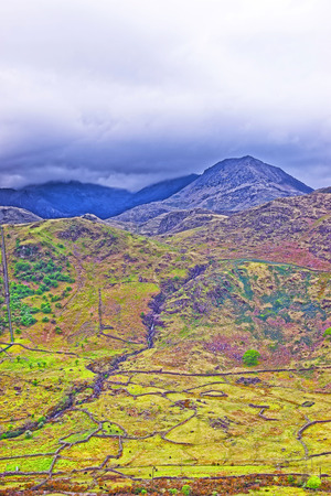 snowdonia: View to a mountain peak in Snowdonia National Park in North Wales of the United Kingdom. Snowdonia is a mountain range and a region in North of Wales.