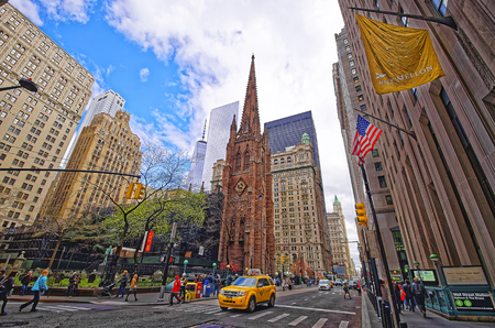 broadway tower: NEW YORK, USA - APRIL 24, 2015: Street view on Trinity Church in Lower Manhattan, New York, USA. It is a historic parish church near Wall Street and Broadway. Tourists nearby