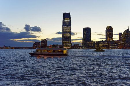 paulus: View from Esplanade of Lower Manhattan, New York, USA, on Ferry and  skylines in Paulus Hook, Jersey City, New Jersey, USA. Skyscrapers illuminated in the evening. Hudson River