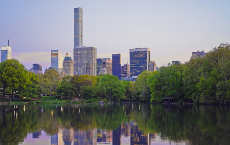manhattan mirror new york: Midtown Manhattan skyline reflected from the water of Central Park.  New York, USA. Skyscrapers illuminated in the evening. Stock Photo