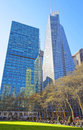 bank of america: NEW YORK, USA - APRIL 25, 2015: Bank of America skyscraper and Green Lawn of Bryant Park in Midtown Manhattan, New York, USA. Tourists relaxing in the park Stock Photo