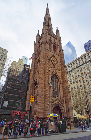 broadway tower: NEW YORK, USA - APRIL 24, 2015: Street view of Trinity Church of Lower Manhattan, New York, USA. It is a historic parish church near Wall Street and Broadway. Tourists nearby
