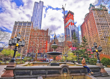 city park fountain: NEW YORK, USA - APRIL 24, 2015: Fountain in City Hall Park with tourists in Lower Manhattan, New York, USA. Skyscrapers on the background.