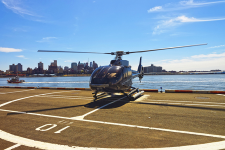 helipad: Black Helicopter on helipad in Lower Manhattan New York, USA, on East River. Pier 6. East River and skyscrapers on the background