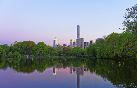 manhattan mirror new york: Manhattan skyline mirrored from water in Central Park.  New York, USA. Skyscrapers illuminated in the evening. Stock Photo