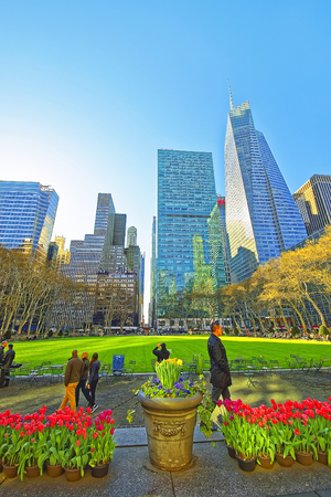 bryant: NEW YORK, USA - APRIL 24, 2015: Skyline with Skyscrapers and tourists in Bryant Park in Midtown Manhattan, New York, USA. Tourists relaxing in the park