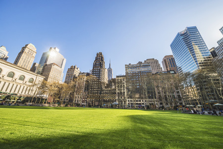 bryant park: Green Lawn and Skyscrapers viewed from Bryant Park in Midtown Manhattan, New York, USA. Tourists relaxing in the park Stock Photo