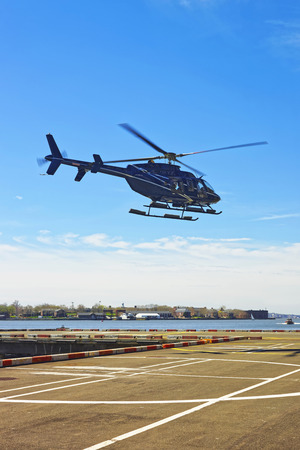 helipad: Black Helicopter landing on helipad in Lower Manhattan New York, USA, on East River. Stock Photo