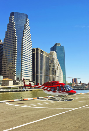 helipad: Helicopter on the helipad in Lower Manhattan New York, USA, on East River. Pier 6. Skyscrapers on the background