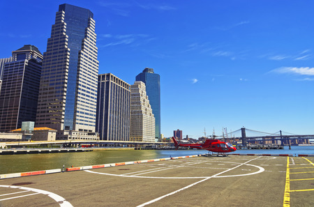 heliport: Red Helicopter on helipad in Lower Manhattan New York, USA, on East River. Pier 6. Skyscrapers, Brooklyn Bridge and Manhattan Bridge on the background