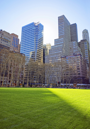 bryant: Skyline with Skyscrapers and Green Lawn in Bryant Park in Midtown Manhattan, New York, USA. Tourists relaxing in the park