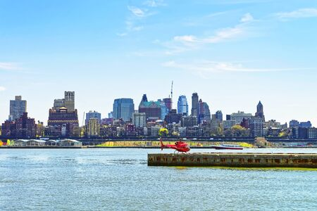 helipad: New York, USA - April 25, 2015: Helicopter on helipad in Pier 6 in Lower Manhattan, New York, USA, East River. Skyscrapers of Brooklyn on the background.
