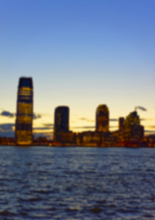 paulus: View from Esplanade of Lower Manhattan, New York, USA, on skyline in Paulus Hook, Jersey City, New Jersey, USA. Skyscrapers illuminated in the evening. On Hudson River. Blurred.