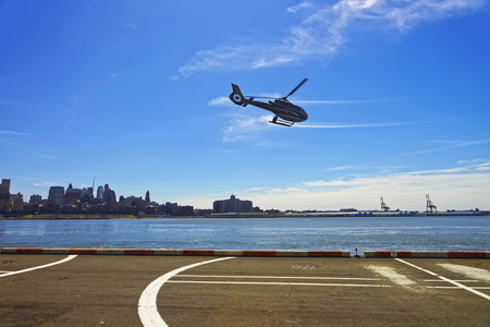 helipad: New York, USA - April 25, 2015: Black Helicopter over from helipad in Lower Manhattan in New York, USA, on East River. Pier 6. East River and skyscrapers of Brooklyn on the background