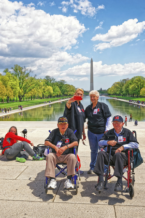 nonprofit: Washington DC, USA - May 2, 2015: War Veterans and guardians of Honor Flight of Middle Tenessee non-profit organization at Lincoln Memorial Reflecting Pool. Washington Monument on the background.