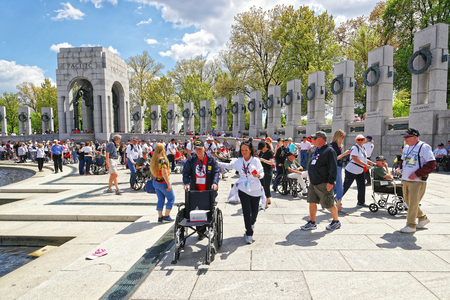 world war two: Washington DC, USA - May 2, 2015: Tourists and War Veterans and guardians of Honor Flight nonprofit organization at National World War Two Memorial, National Mall. Pacific Arch on the left Editorial
