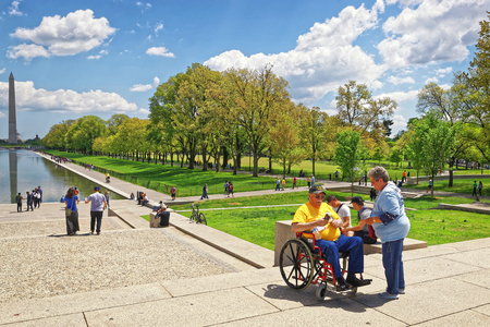 nonprofit: Washington DC, USA - May 2, 2015: War Veteran and his guardian from Honor Flight near Lincoln Memorial Reflecting Pool. Washington Monument on the background.