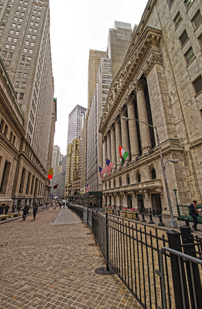 nyse: NEW YORK, USA - APRIL 24, 2015: Street view of New York Stock Exchange on Wall Street, Lower Manhattan, USA. It is called NYSE in short. Tourists in the street