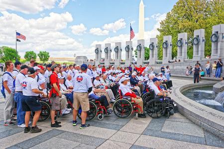 nonprofit: Washington DC, USA - May 2, 2015: Tourists and group photo of War Veterans, members of Honor Flight Central Florida nonprofit organization, Pillars on National World War 2 Memorial, National Mall