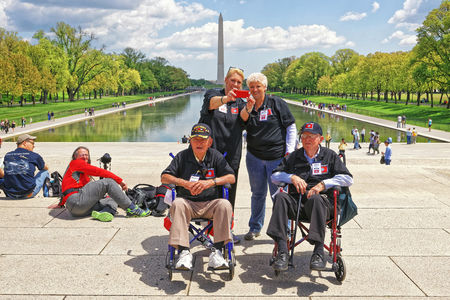 Washington DC, USA - May 2, 2015: War Veterans and guardians of Honor Flight of Middle Tenessee non-profit organization near Lincoln Memorial Reflecting Pool. Washington Monument on the background.
