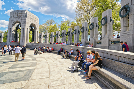 nonprofit: Washington DC, USA - May 2, 2015: Tourists and War Veterans and guardians of Honor Flight nonprofit organization in National World War Two Memorial, National Mall. The Pacific Arch on the left
